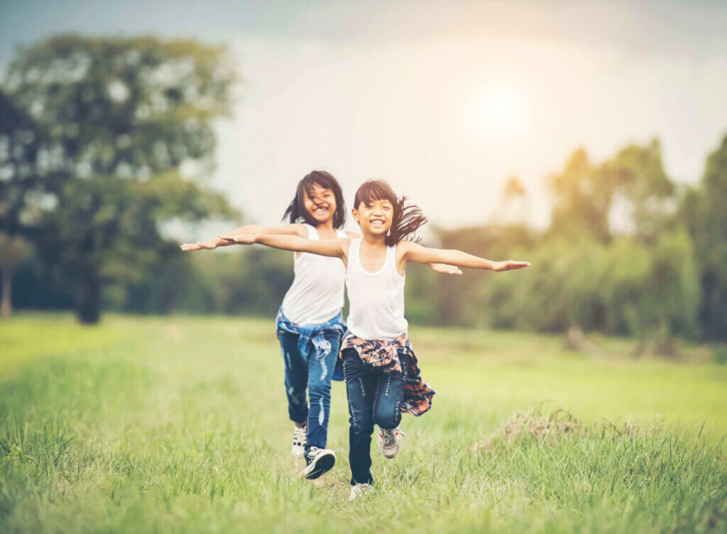 Two little cute girls are running on green grass. Best friends.